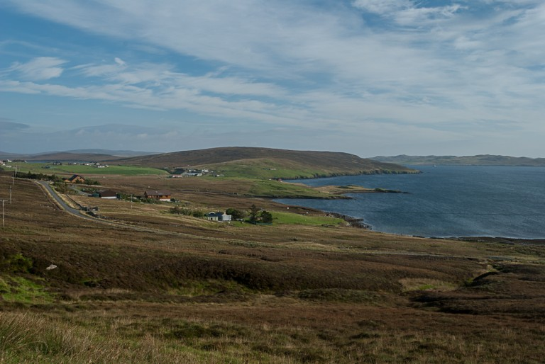 A first view of Shetland, with fjords, rolling green hills and blue sea